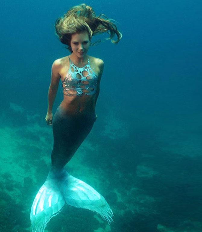 Настоящая русалка улыбается под водой.